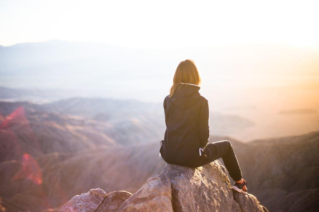 développement personnel femme en haut d'une montagne face au soleil