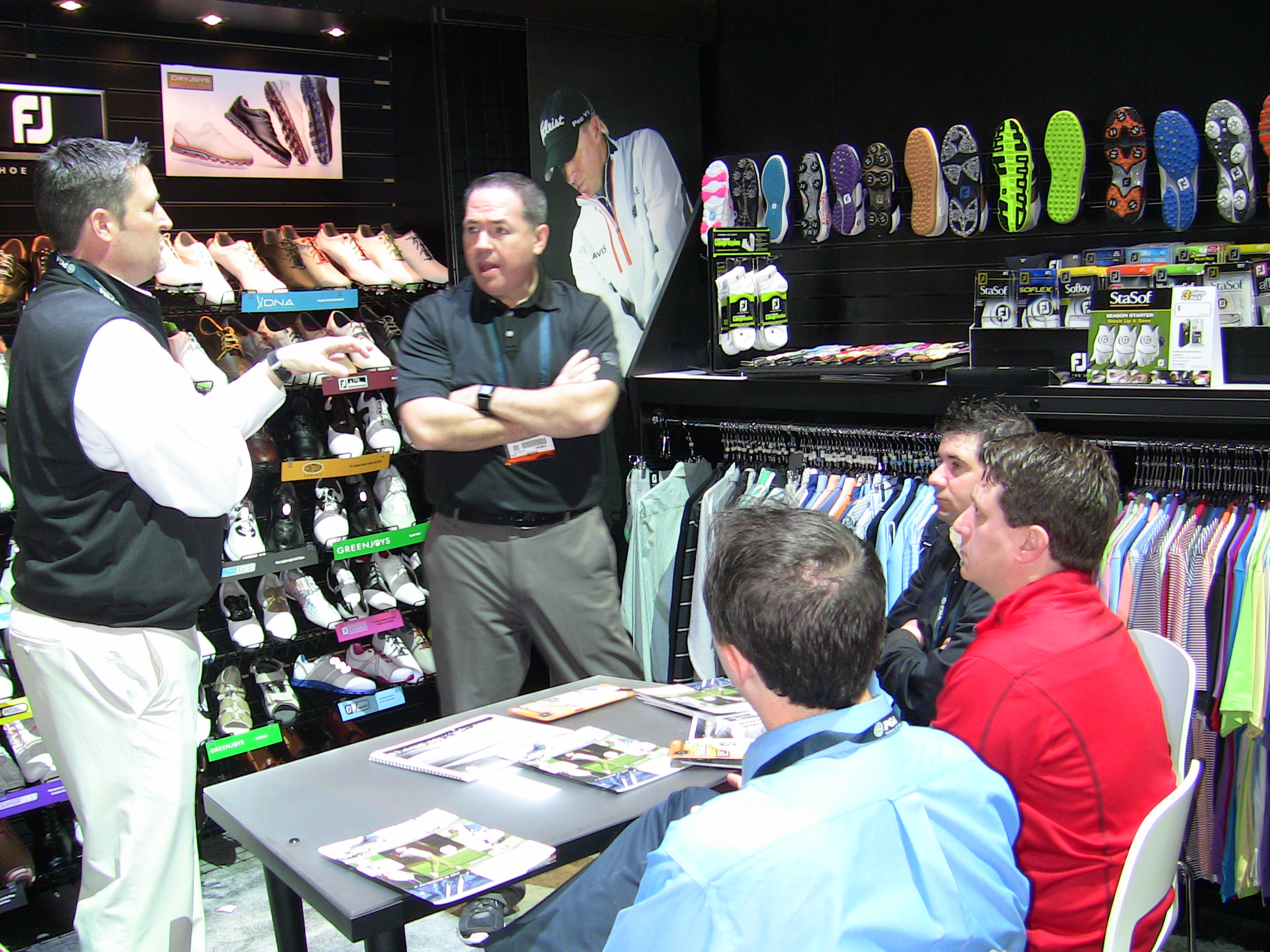 Tom Cox (center), president and CEO of Golfballs.com, and members of the Golfballs.com staff meet with a FootJoy representative during the PGA Merchandise Show, looking at the newest line of FootJoy's golf apparel.
