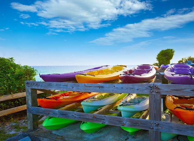 A rack holds three rows of kayaks in purple, lime green, red and yellow hues.