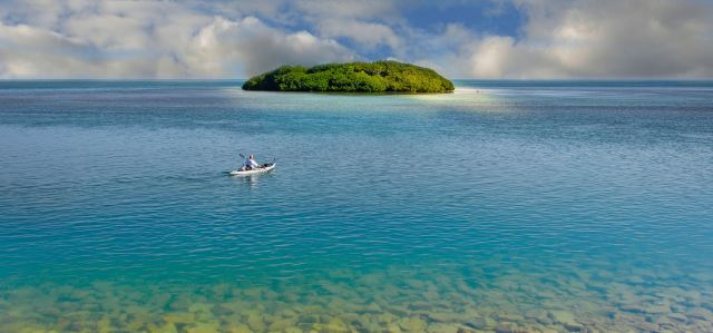 A lone kayaker paddles out to a remote island.