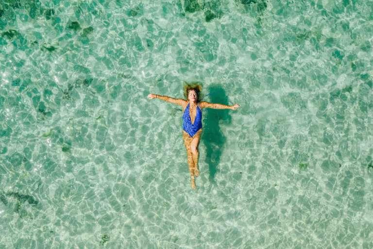 Tranquilidade, segurança, paz: mulher deitada no mar de água calma e transparente
