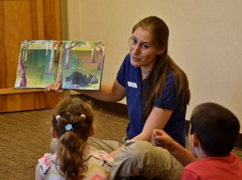 A Great Parks employee reads a story to children.