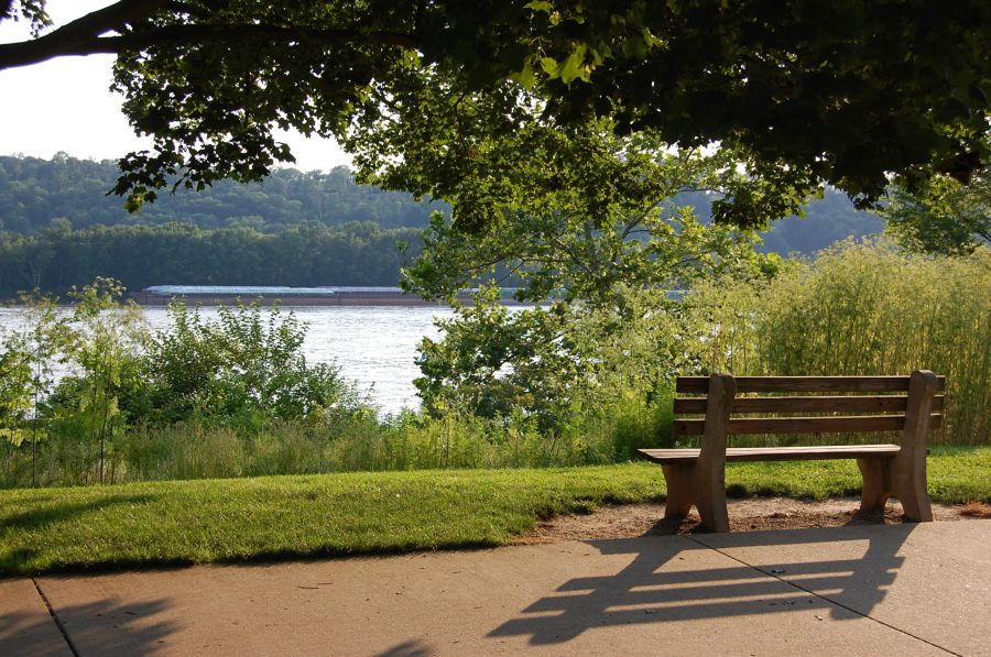 A park bench sits empty on a paved path that overlooks the Ohio river. It is a sunny afternoon. A barge is traveling down the river.