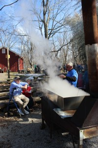 A man and woman sit to the left watching a Great Parks volunteer (to the right) boil maple sugar, turning it into maple syrup.