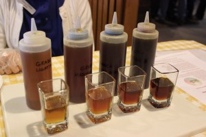 Four shot glasses are filled to show the differences in grades of maple syrup. From left to right, the maple syrup ranges from a golden color, to amber, to chestnut to a deep brown.