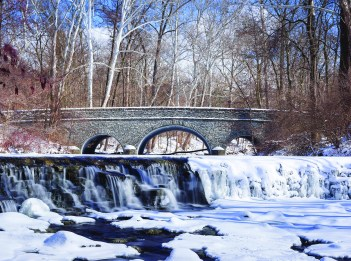 Buckeye Falls at Sharon Woods is half-frozen while the other half is covered in snow. A bridge in the background is also covered in snow.
