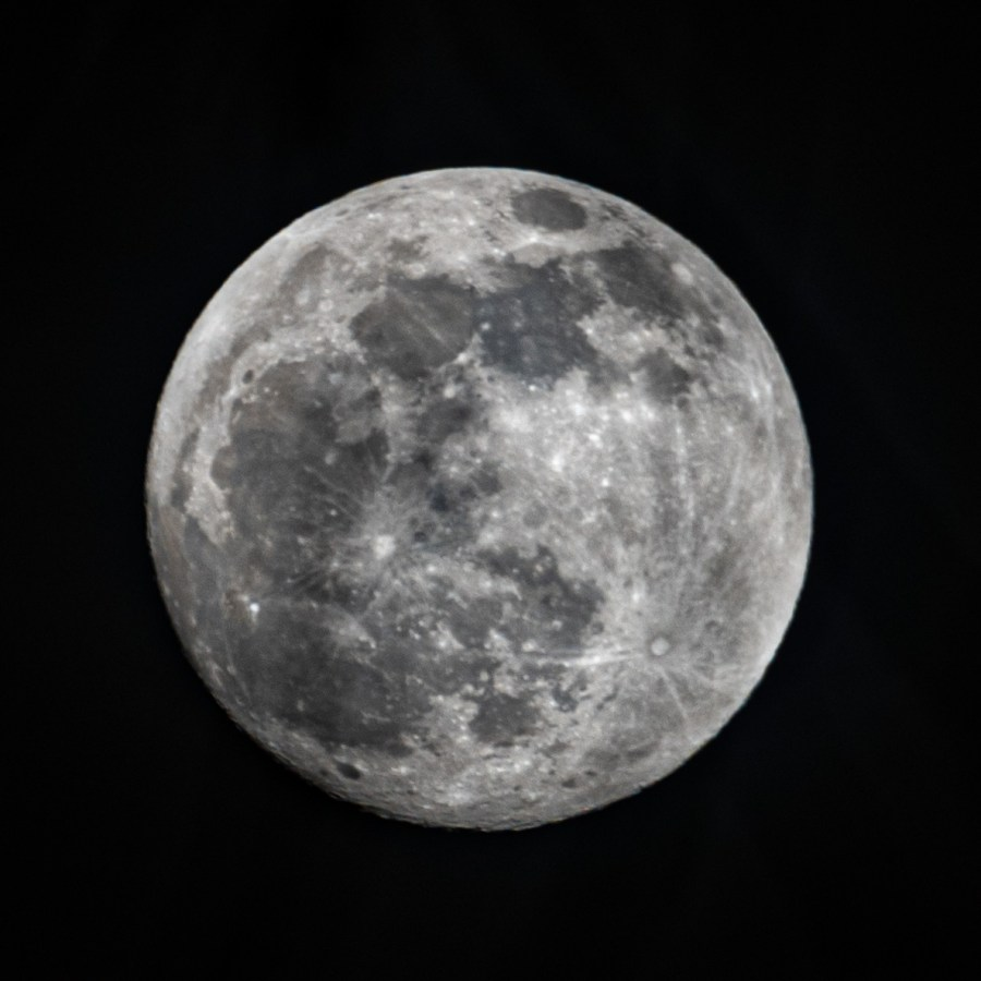 A full moon shows craters and dark areas on its surface.