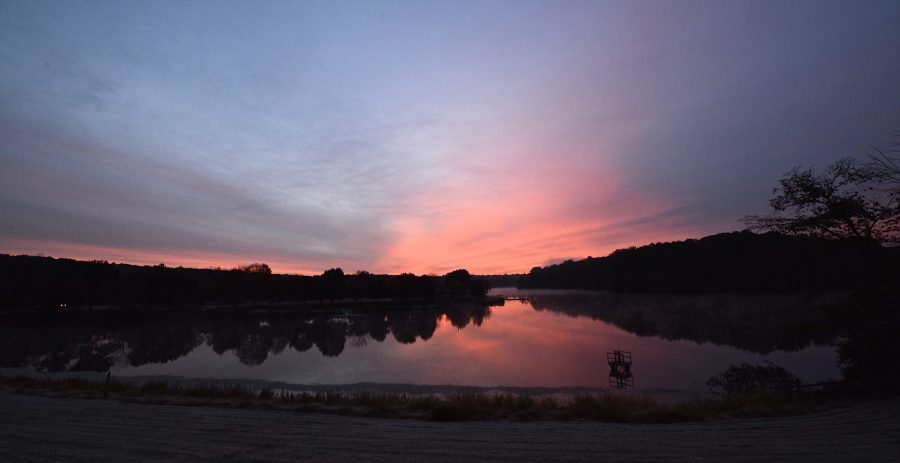 The sun rises over Miami Whitewater Forest Lake/ The sky is shades of pale pink and blue.