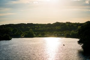 The sun begins to set over the green forest and Winton Lake.