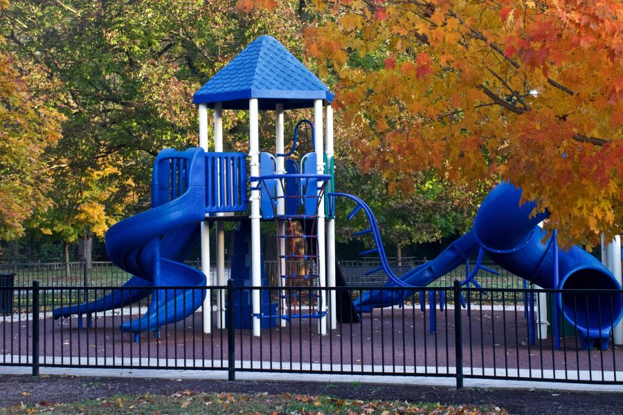 The bright blue Fernbank Park playground stands out against the red and orange fall foliage.