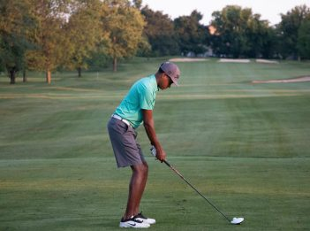 A man lines up his shot at The Mill Course on a sunny evening.