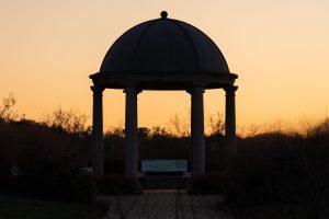 The sun sets over a gazebo, making the sky orange.