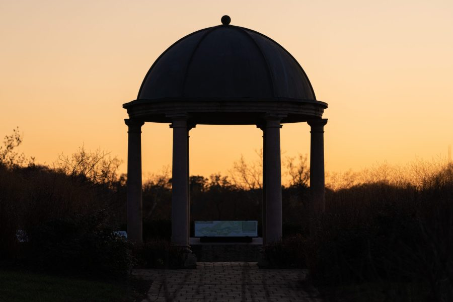 The sun sets over a gazebo, making the sky a pale orange.