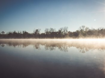 The sun shines over Winton Lake. You can see the reflection of the trees lining the lake in the water. There is fog permeating from the surface of the water.