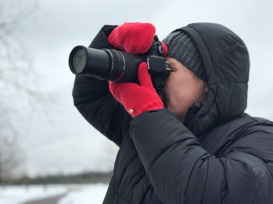 A man wears red mittens, a black coat and a black hat while taking a photo with his camera on a snowy winter day.