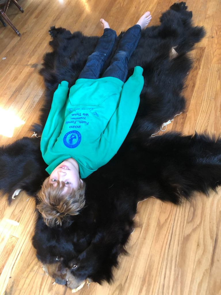A young boy lays on top of a black bear belt.