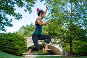 A young woman balances on a slackline on a sunny summer day.