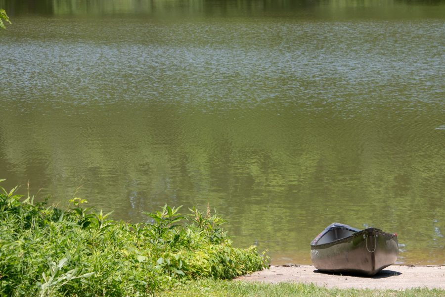 A canoe sits on the bank of a lake.