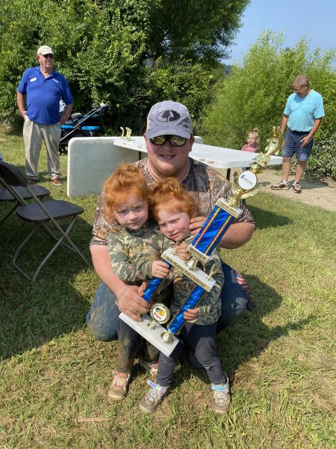 Makenzi with her winning trophy at the Kids' Mystery Fish Challenge on July 24, 2021. She poses with her twin sister and dad.