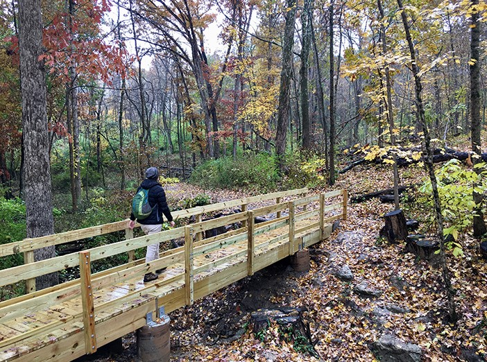 Person crosses wooden bridge on trail in woods