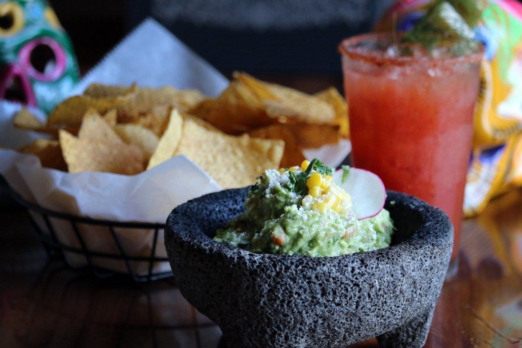 Basket of tortilla chips and bowl of guacamole at Verde Flavors of Mexico