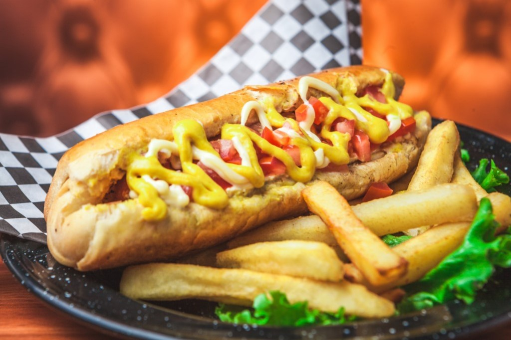 Delicious hot dog covered in toppings next to fries at a Portillo's fundraising event