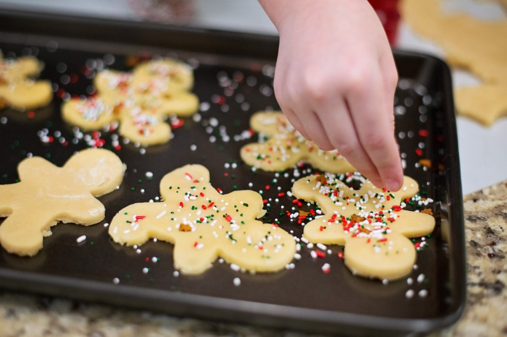 Hand putting sprinkles on gingerbread man cookies for a bake sale fundraiser