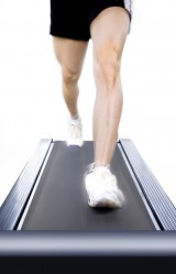 Guy walking on treadmill with only legs and feet showing front view