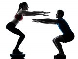 Personal trainer doing a squat with his female client doing one too