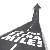 "Street turning into an arrow with white paint on it saying ""Go the Extra Mile"""