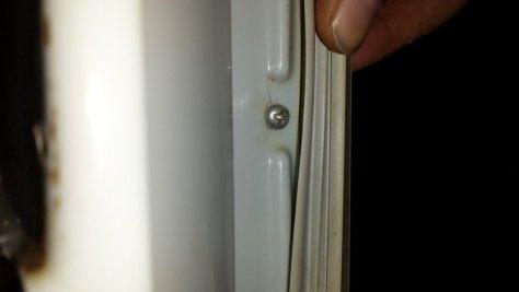 Tornillos que sujetan el panel y el cierre imantado de la puerta