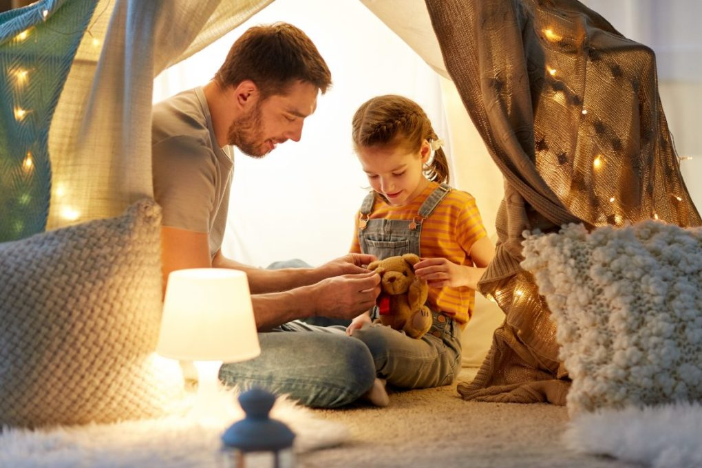 Dad playing in a warmly lit homemade blanket and pillow fort with his young daughter
