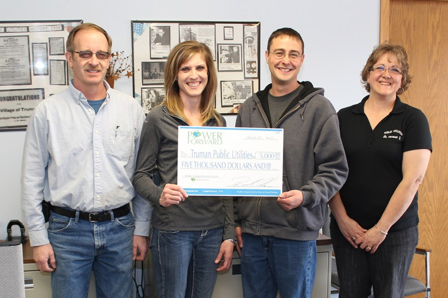 Heartland Communications Manager Ann Hyland, second from left, presents an energy efficiency grant to Truman Commission Chair Brad Nickerson, Public Utilities Foreman Justin Anderson and Public Utilities Office Manager Judi Davis.