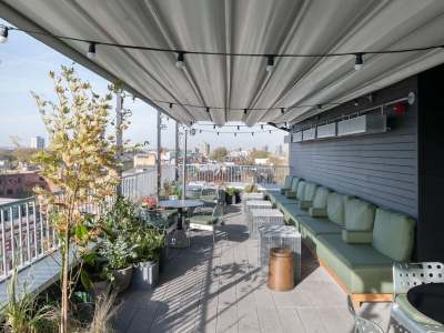 rooftop bar with cover, seating,, plants and round tables and chairs