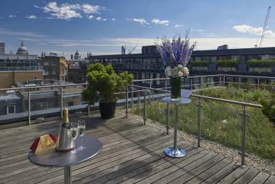 rooftop terrace with tall tables and plants