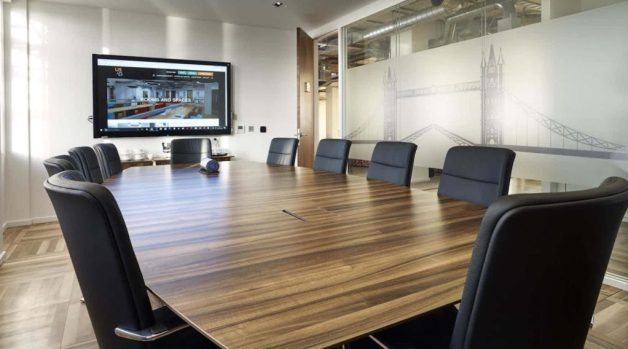 meeting room with long wooden table and black leather chairs with tv screen