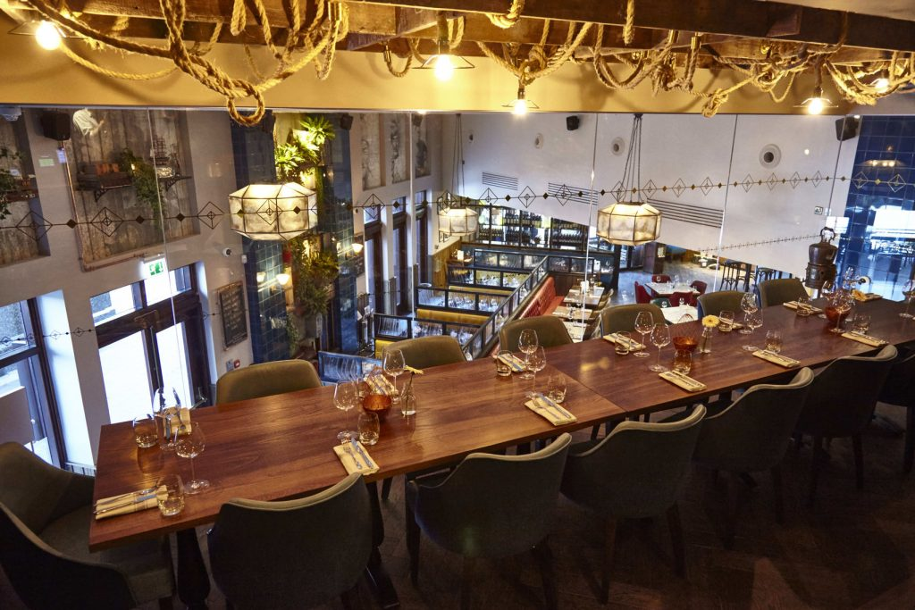 A top angle photo of the private dining room at the Tea Merchant pub. A long table with one glass wall that looks over the pub below