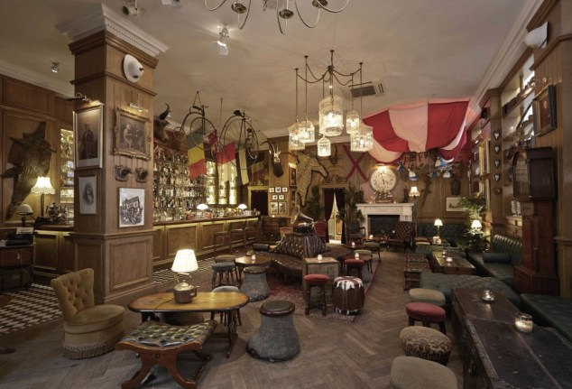 A large room with pictures and objects on the walls, a bar along one side and several mismatched tables, chairs and stools in the centre.