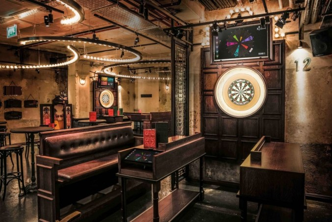 a quirky bar has 2 big dart boards set up on the walls surrounded by booth seating. There are quirky light fixtures handing on the ceiling