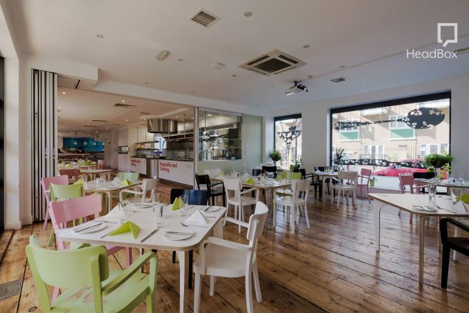 Large restaurant Space with pastel green and pink tables and chairs arranged throughout the Space. Large floor to ceiling windows line the right hand wall looking out onto the street.