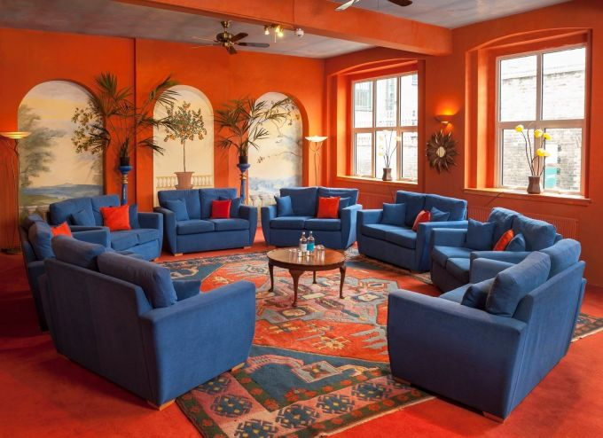 bright orange room with blue sofas