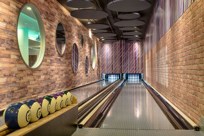 This shot shows a modern bowling alley with exposed brick walls and big circular windows. The lanes look clean and shiny, all the pins are the far end of the bowling lane are standing up right and there are 7 bowling balls lined up on the rack.