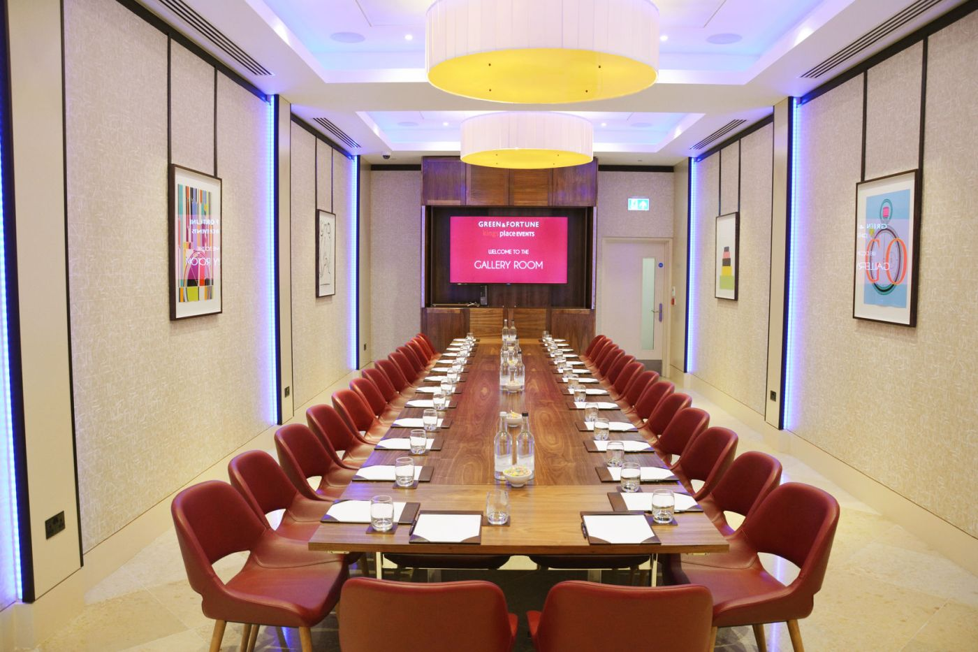 A long table with red chairs in a meeting room