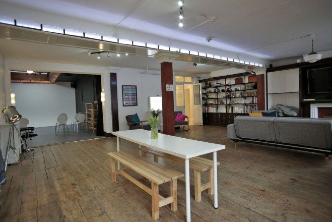 in the centre of bust studio there is a white picnic table with flowers on top of it and a grey sofa in the background. on the back wall is a dark brown shelf with books standing in it. Through an archway you can see a photography studio with white walls and lighting equipment