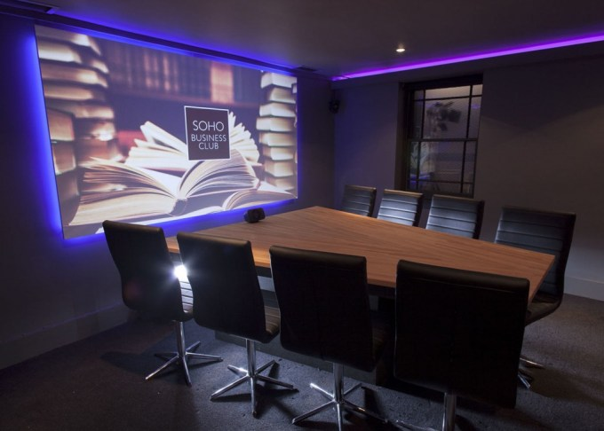Intimate dark meeting and screening room. A angular table is surrounded by 8 chairs angled towards a large cinema screen backlit in blue LED lighting.