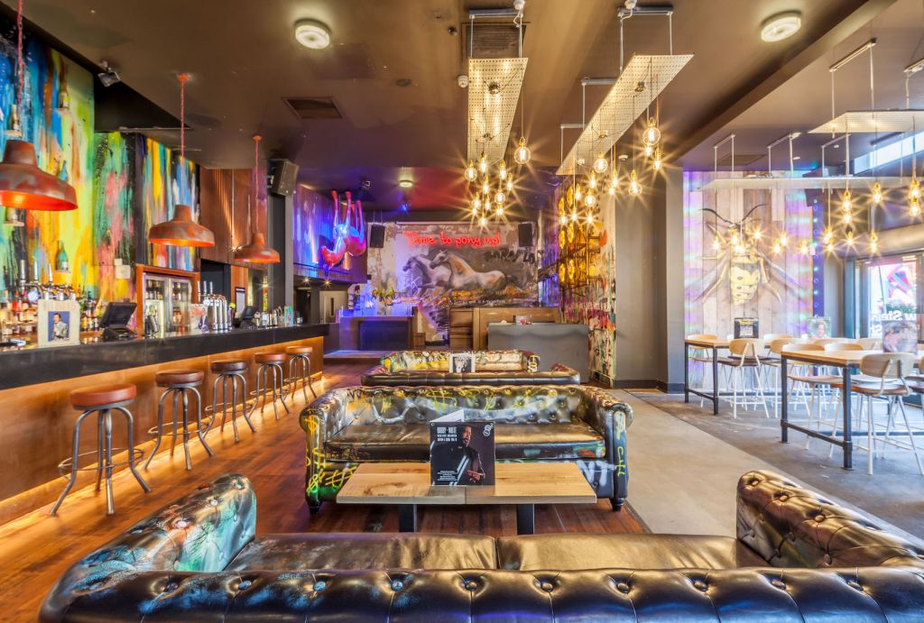 bar with leather sofas bright lighting and graffiti art on the walls