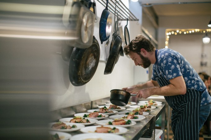 man in apron holding a saucepan