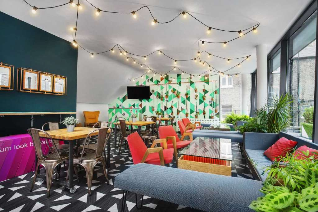 A bright and colourful event Space with black and white patterned floor, fairy lights hanging from the ceiling and bright orange chairs