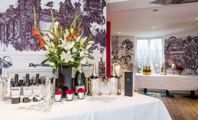 a large table is set up for a drinks reception with a white table cloth, bottles of wine, glasses, candles and a large floral centre piece with whit and orange lily's. The wall have hand drawn artwork on them and then floor is wooden.