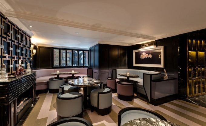 a large bar area with marble table and comfy leather stools pushed around them. There are wooden frames on the wall and a large window on the back wall.